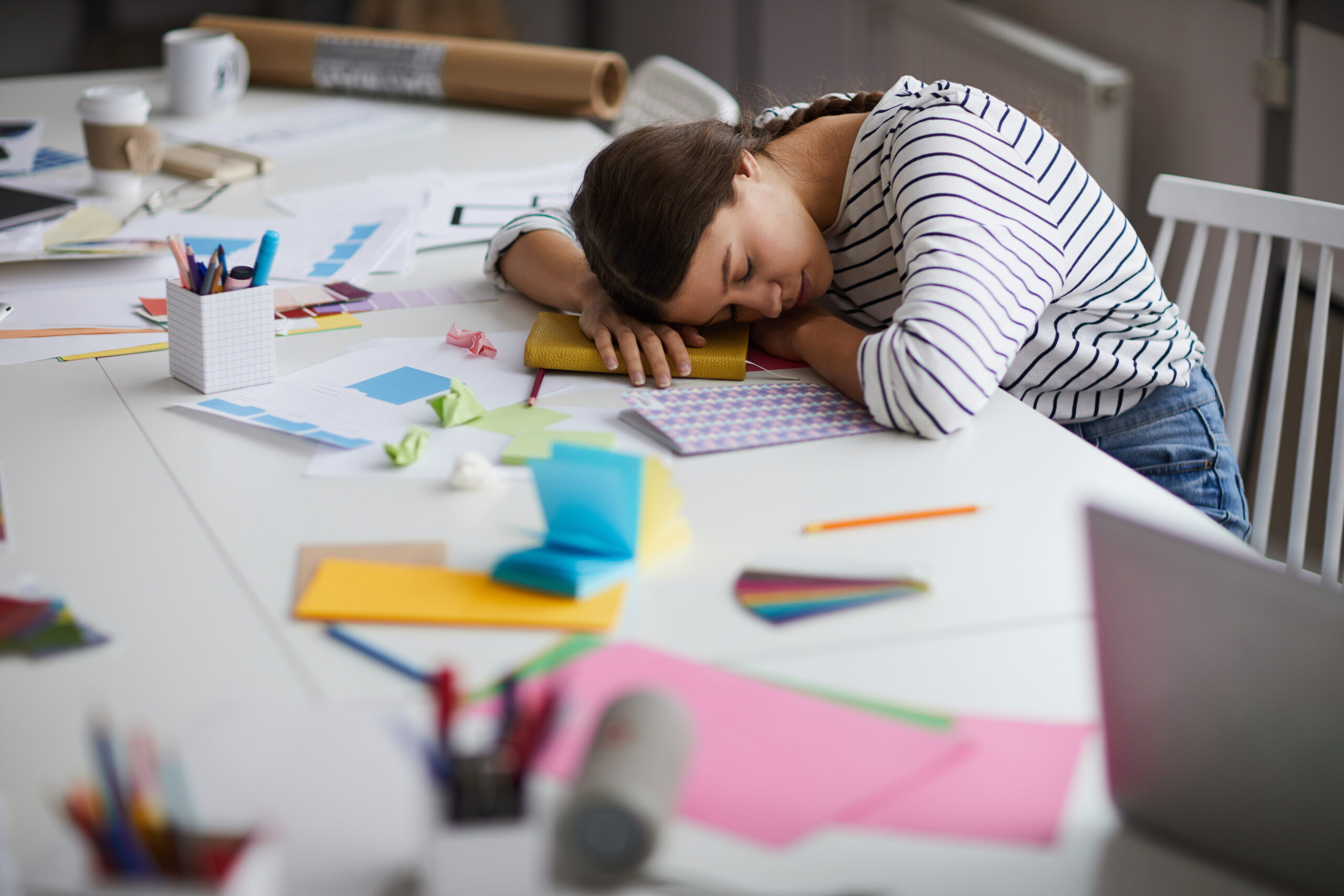 exhausted young woman sleeping at work AMYVU2X scaled