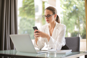 serious businesswoman using smartphone in workplace 3761520